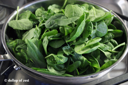 raw spimach in pan to cook for baked fish stuffed with spinach & feta